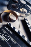 Movie slate and film reel on wood. Movie clapper and film reel on a wooden backgorund Royalty Free Stock Photo