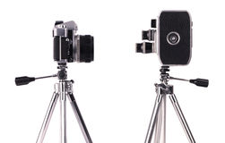 Movie and still cameras. Vintage 35mm SLR camera and vintage 8mm movie camera on a compact tripod Royalty Free Stock Photos