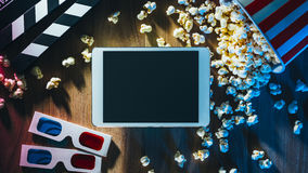 Movie streaming app. Blank digital tablet, popcorn, 3D glasses and filmstrip, cinema and movie online streaming concept Royalty Free Stock Photo
