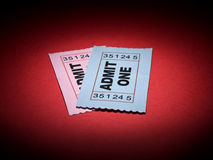 Movie stub. Close up shot of two generic admission tickets over red background Royalty Free Stock Photo