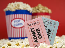 Movie stubs and popcorn. Two popcorn buckets over a red background. Movie stubs sitting over the popcorn Royalty Free Stock Images