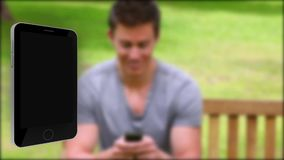 Movie tapes appearing from a bright smartphone with man in a park on background Stock Images