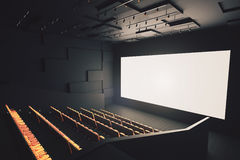 Movie theater with blank screen. Side view of movie theater interior with rows of seats and blank white screen. Mock up, 3D Rendering Royalty Free Stock Images