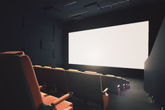 Movie theater with empty screen. Side view of movie theater interior with rows of seats and empty white screen. Mock up, 3D Rendering Royalty Free Stock Photos