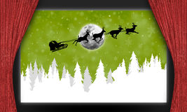 Movie theater with Santa Claus. Santa Claus silhouetted with sleigh and reindeer against green skies and snowflakes behind red velvet curtains on movie theater Stock Photos
