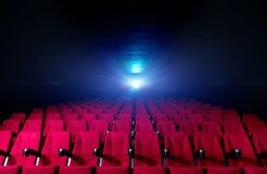 Movie theatre hall with red seats. And working projector with beams of light royalty free stock photos