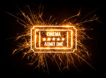 Movie ticket in glowing sparkler on dark background. Stock Photos
