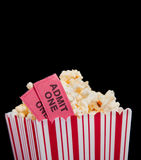 Movie ticket and popcorn on a black background royalty free stock image
