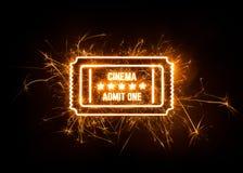 Movie ticket in sparks on dark background. Stock Photos