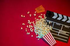Movie tickets, clapperboard, pop corn on red background.  Stock Photo