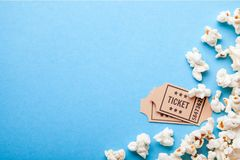 Movie tickets and popcorn on blue background. Copy space for text.  Stock Photography