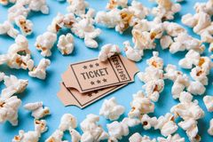 Movie tickets and popcorn on blue background stock images