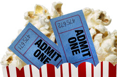 Movie Tickets And Popcorn Isolated. Close up or macro shot of two blue movie tickets in a small tub full of delicious popcorn.  Shot on white background Stock Photos