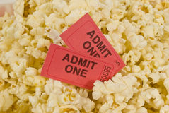 Movie Tickets and Popcorn. Two red movie tickets sits in a background of popcorn Royalty Free Stock Photo