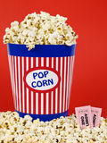 Movie for two. A popcorn bucket over a red background. Movie stubs sitting over the popcorn Stock Photography
