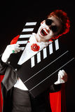 Movie vampire. Portrait of a extravagant vampire with a clapper board. Halloween. Cinema industry royalty free stock photography