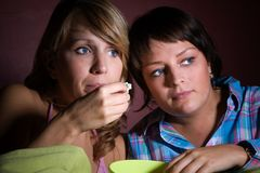 Movie watching. Two girls watching a scary movie together while eating popcorn Royalty Free Stock Image