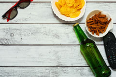 Movie watching home party concept. Person watching movie alone - top view with bottle of beer, salted snacks, remote control and TV glasses on the table in loft Royalty Free Stock Images