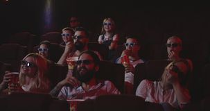 Moviegoers watching comedy movie in cinema. Medium shot of moviegoers watching comedy movie in cinema stock video