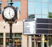 Movieland movie theater marquee listing films and old style roman numeral round clock on pole. Glass windows, downtown Schenectady New York stock images