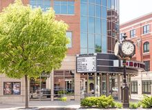 Movieland movie theater marquee listing films and old style roman numeral round clock on pole. Glass windows, trees, downtown Schenectady New York stock photography