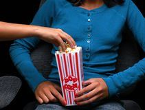 At the movies. Girl holding popcorn at the movies with friend reaching into bucket Stock Images