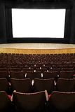 At the movies. Empty movie screen, black open curtain, wooden stage, wooden seats Stock Photos