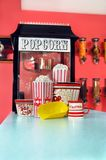 At the movies. Counter has commercial sized popcorn popping machine, popcorn cartons, popcorn, dipper and butter royalty free stock photo