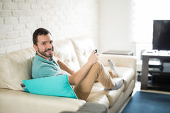 Movies afternoon. Attractive man wearing casual clothes and relaxing in the living room watching some movies Stock Image