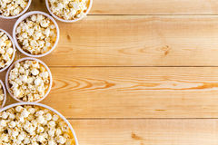 Movies background with popcorn bowls on table. Movies background with various sized full popcorn bowls on table from top down perspective Stock Images