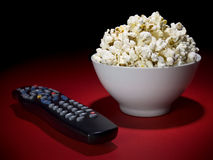Movies at home. A popcorn bowl and a remote control ready for fun Stock Photography