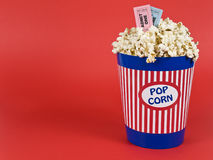 Movies for two. A popcorn bucket over a red background. Movie stubs sitting over the popcorn Royalty Free Stock Photo