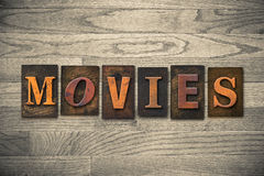 Movies Wooden Letterpress Theme. The word MOVIES theme written in vintage, ink stained, wooden letterpress type on a wood grained background Stock Photos