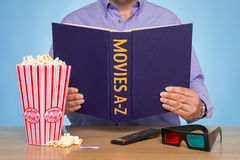 Movies A-Z. A man sat at a table reading a MOVIES A-Z book Royalty Free Stock Image