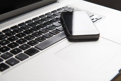 Movil telefon på en bärbar dator Royaltyfri Bild