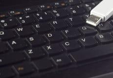 Movimentação branca do flash de USB em um usb preto do teclado fotos de stock