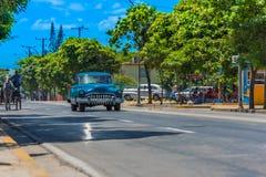 Movimentação clássica americana azul do carro na calha Varadero Cuba da estrada com o transporte no lado da rua Foto de Stock