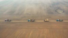 Movimentação da maquinaria de exploração agrícola na estrada aos campos agrícolas à opinião aérea de colheitas de planta vídeos de arquivo