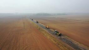 Movimentação da maquinaria de exploração agrícola na estrada aos campos agrícolas à opinião aérea de colheitas de planta video estoque