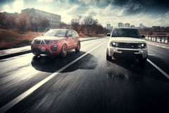 Movimentação de Rover Range Rover da terra dos carros na estrada de cidade do asfalto no dia ensolarado do outono Imagens de Stock Royalty Free