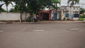 Movimentação do carro do 'trotinette' da bicicleta ao longo da rua da cidade por lojas das casas de palmas video estoque