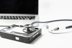 Movimentação do estetoscópio e de disco rígido no fundo branco Diagnóstico do material informático e conceito do reparo foto de stock