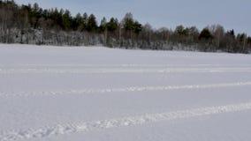 Movimentações do carro de neve ao longo do vale nevado vasto cruzado por trilhas video estoque