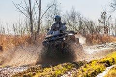 Movimentações do piloto de ATV através da lama e da água Fotografia de Stock