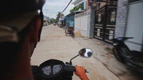 Movimentações do 'trotinette' do close up ao longo da rua da cidade por lojas das casas vídeos de arquivo