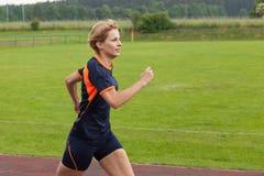 Movimentar-se da mulher exterior em uma pista de corridas Imagens de Stock