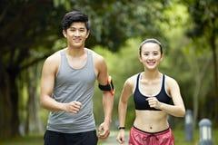 Movimentar-se de corrida dos pares asiáticos novos em um parque Fotos de Stock Royalty Free