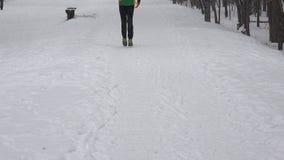 Movimentar-se e mulher do homem do corredor com o pram no trajeto nevado no parque do inverno 4K video estoque