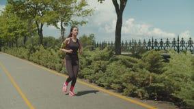 Movimentar-se fêmea desportivo ao longo do trajeto de corrida no parque video estoque