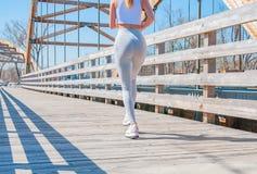 movimentar-se A mulher bonita está correndo através da ponte imagem de stock royalty free